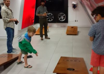 Family place corn hole on boards made by Wilmington NC nonprofit kids work it at the 2019 Audi Cape Fear Quattroberfest